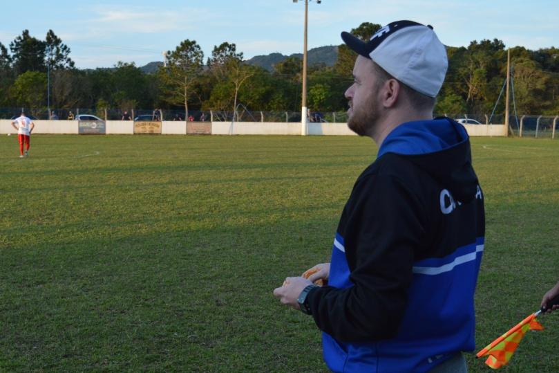 O técnico do Grêmio, Djone Kammers, bem de buena descascando sua bergamota enquanto orientava seu time em busca do gol da classificação. (Foto: Lucas Gabriel Cardoso)