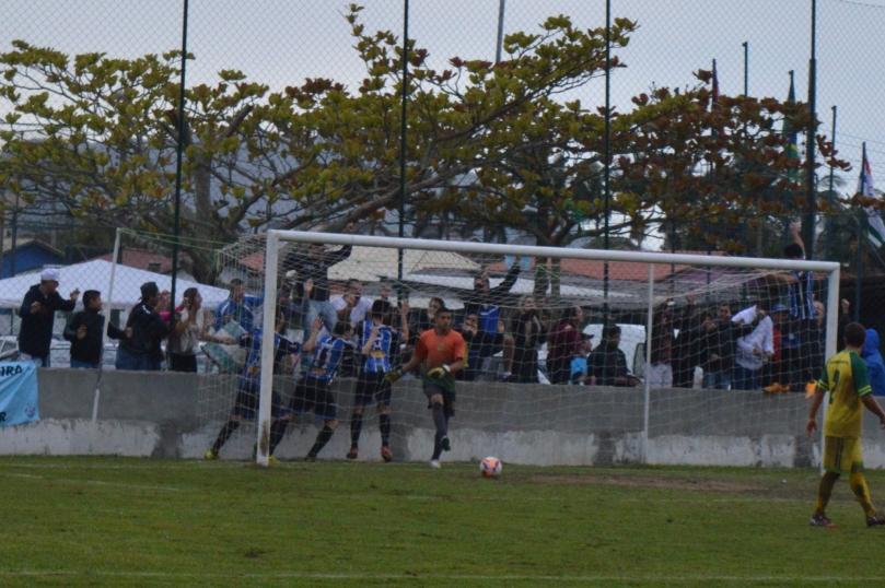 João Vitor buscando a bola dentro do gol, enquanto o Grêmio comemorava com a torcida, ao fundo. (Foto: Lucas Gabriel Cardoso)
